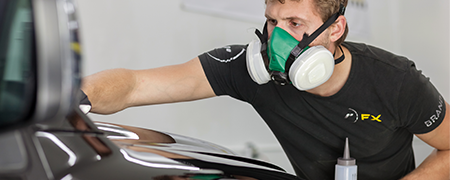 A RestorFX Technician wearing a mask chemically restoring a vehicle's damaged paint surface