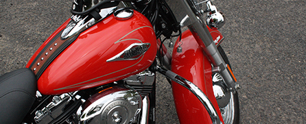 A clean and shiny motorcycle showing its brilliant red tank and fender