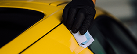A RestorFX Technician protecting the painted surface of a brilliant yellow sports car with ClearFX Exterior product