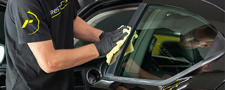 A RestorFX Technician wiping off the plastic trim of a car door as part of restoring it
