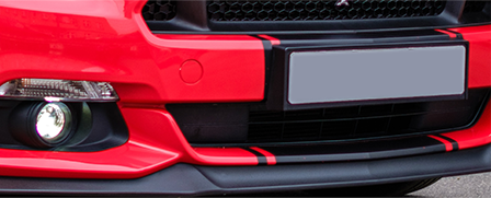 Front of a shiny, pristine red car showing its brilliant black grill and trim around the plate and bumper