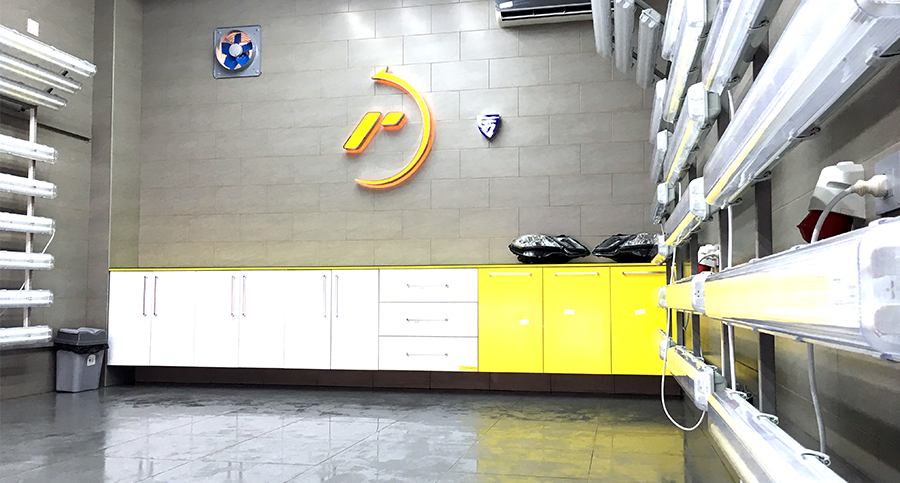 Pristine work area inside a RestorFX Center with light panels and yellow and white branded shelving and walls
