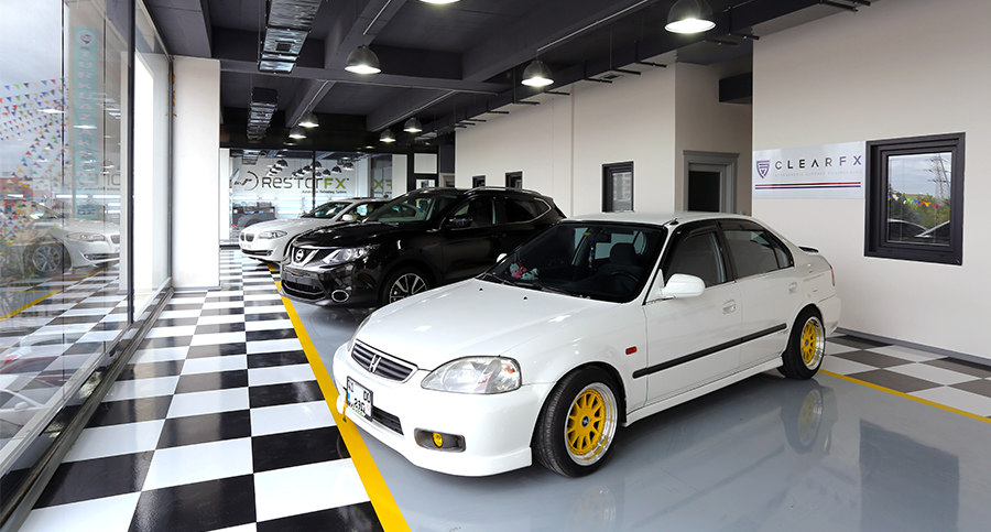 Beautiful, bright showroom inside a RestorFX Center with a row of shiny cars, tall glass windows and office spaces