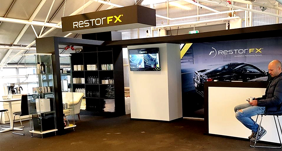 A lustrous black car in a bright RestorFX Center work area with black walls, yellow accent ceiling panel and lights